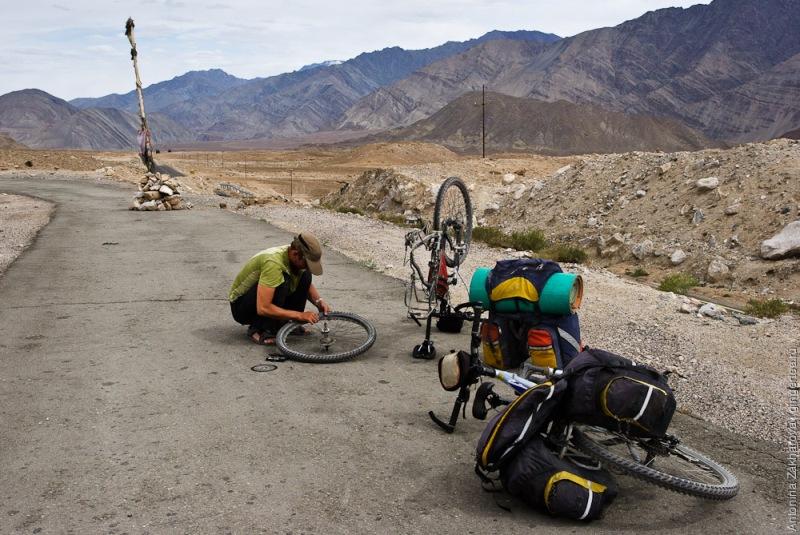 Мужик чинит колесо велосипеда на дороге