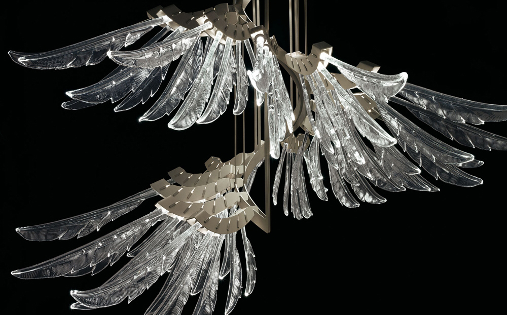 Barovier & Toso Angel – изящные стеклянные перышки, парящие в пространстве, раскрывающиеся в своем неспешном полете, словно эфемерное крыло. Каждое «перо» подсвечено светодиодом. Коллекция представлена двумя подвесными светильниками разной высоты, в трех отделках стекла – прозрачный, коньячный и светло-розовый. Металлическая арматура сложной структуры украшена уникальной отделкой цвета «мирра».