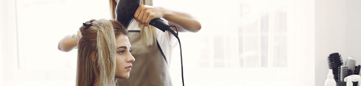 девушке сушат волосы феном