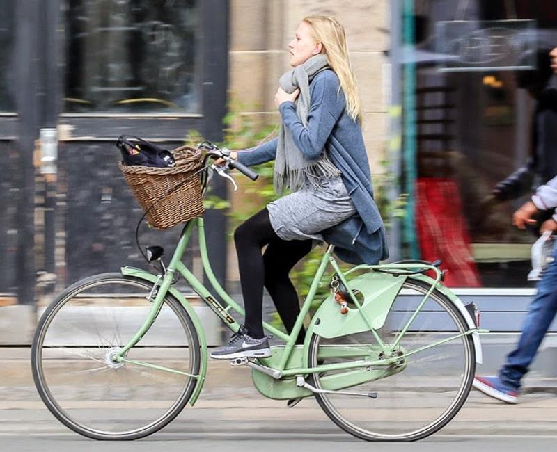 Девушка в плаще на велосипеде с кожухом на цепи