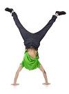 Мальчик в стойке на руках тренирует равновесие.