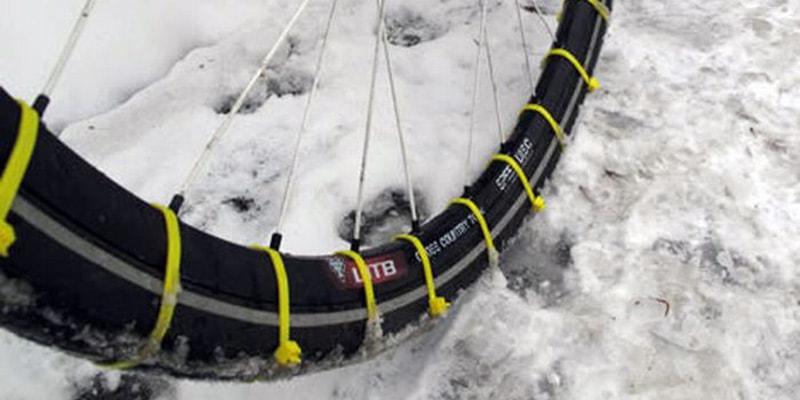 Строительные стяжки на велосипедном колесе для увеличения сцепления с зимней дорогой