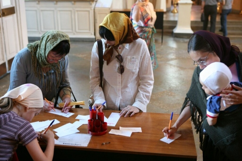 Фото с женщинами, пишущими записки в храме