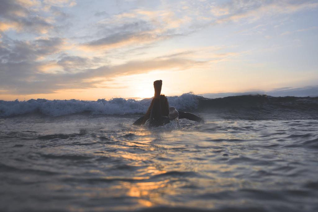 Плывет на доске для серфинга