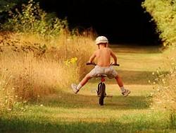 ребенок учится держать равновесие на велосипеде