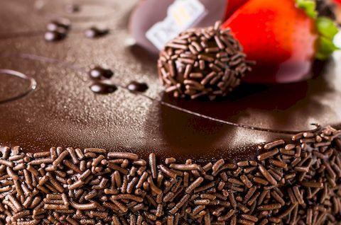Шоколадный торт без глютена украшен ягодой клубникой и кондитерской обсыпкой