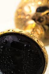 Маленькая золотистая анальная втулка с чёрным кристаллом - 7,2 см.