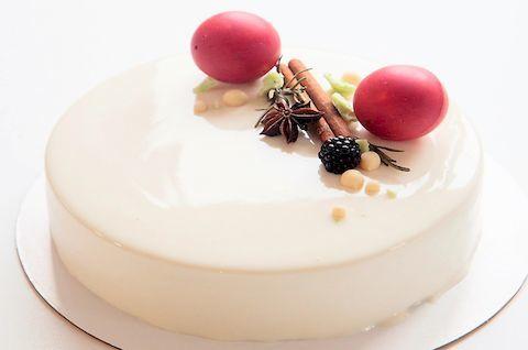 Безглютеновый муссовый торт украшен ягодами и белой глазурью