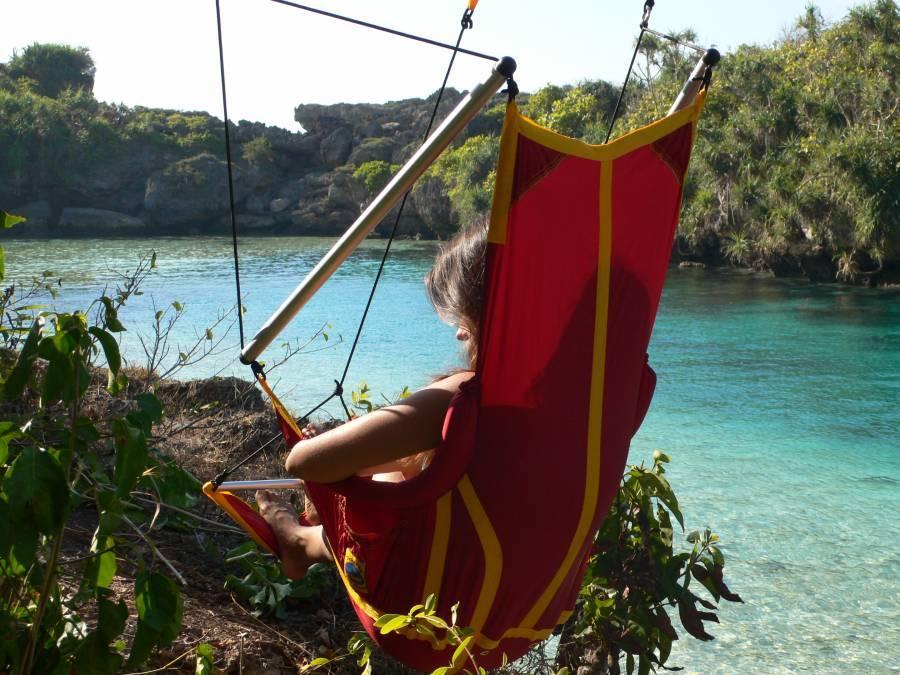 Отдых в подвесном кресле на берегу реки.