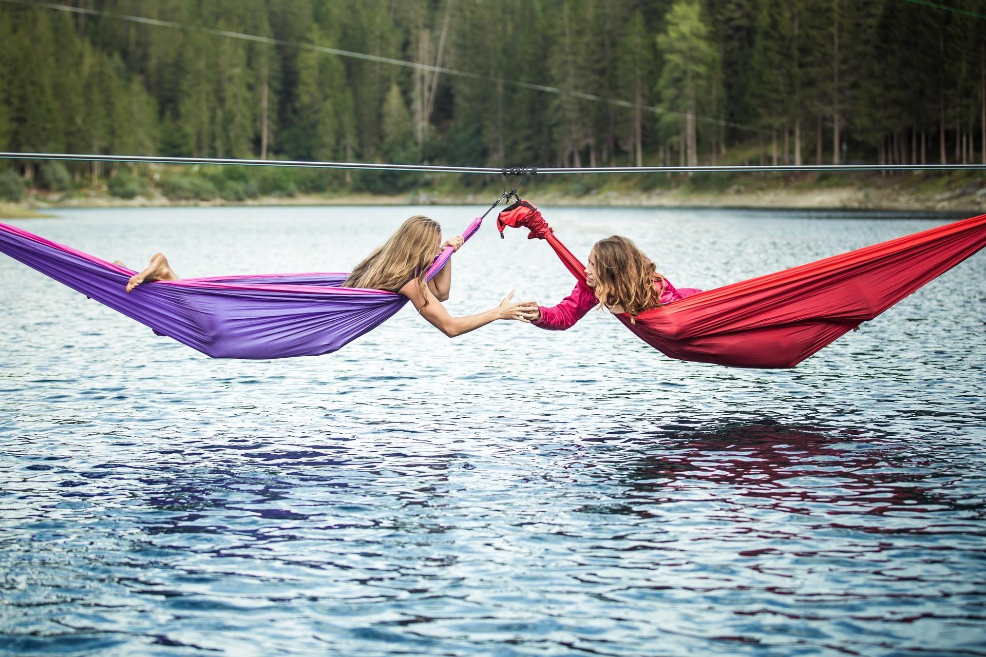Две девушки в гамаках над рекой.