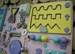 Бизиборд с розовой основой 50х65 см и желто-фиолетовыми деталями