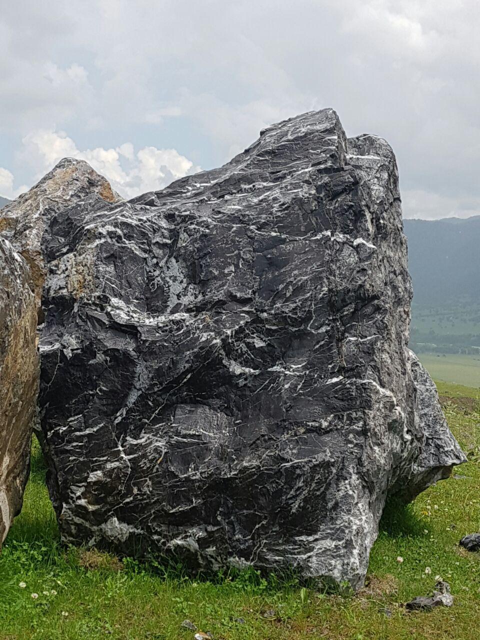 черная мраморная глыба валун, добыча с гор