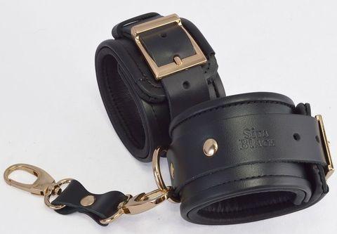 Черные кожаные наручники с золотистыми пряжками и карабином