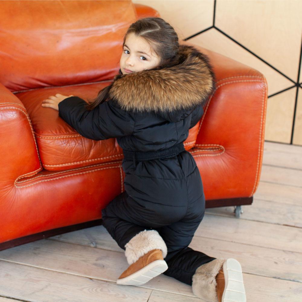 Дитячий однотонний зимовий комбінезон чорного кольору і опушкою з натурального хутра