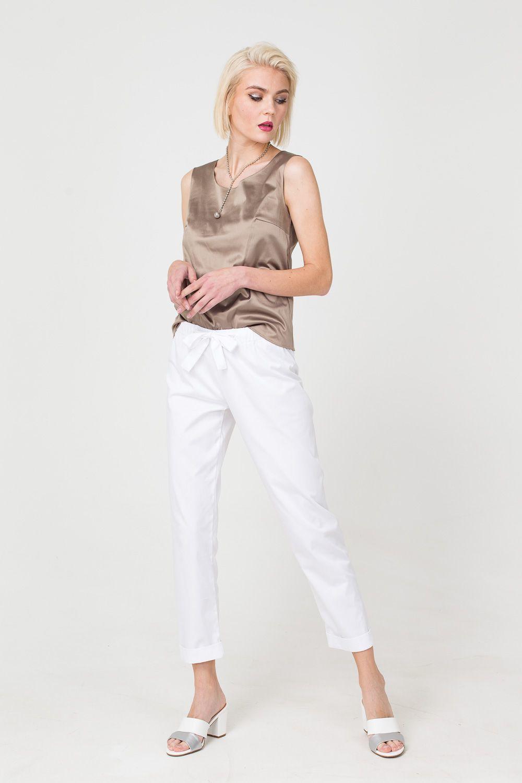 Брюки А402-558 - Белые брюки - прекрасная альтернатива строгим черным. Базовый цвет делает их универсальным спутником любых комплектом. Тактичный белый прекрасно сочетается с самыми яркими цветами и активными принтами. Модель на поясе с бантом отличается комфортной посадкой, укороченная длина смотрится кокетливо и позволяет выбрать любую обувь.