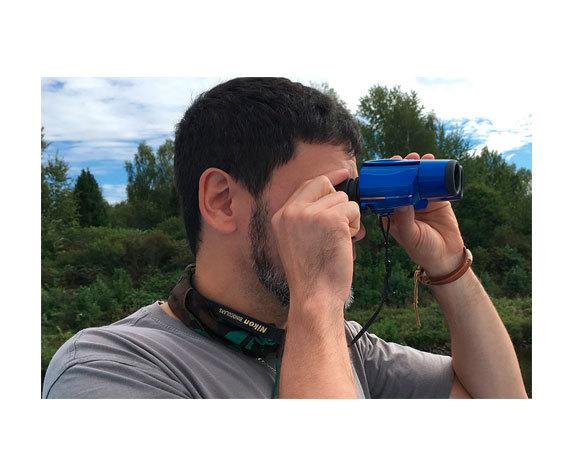 глядит в бинокль Nikon Aculon T11