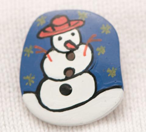 Пуговица-открытка с нарисованным снеговиком в красной шляпе на синем фоне