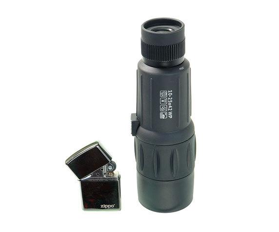 Зажигалка на фоне монокуляра Veber 10-25x42