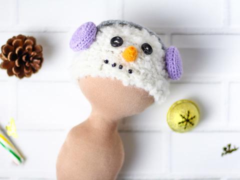 Шапка в'язана ручної роботи для ляльки  - Сніговик у бузкових навушниках