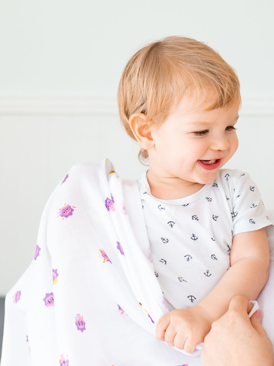Имиджевое фото малыша с муслиновым одеялом Adam Stork лимитированной коллекции с малышариками