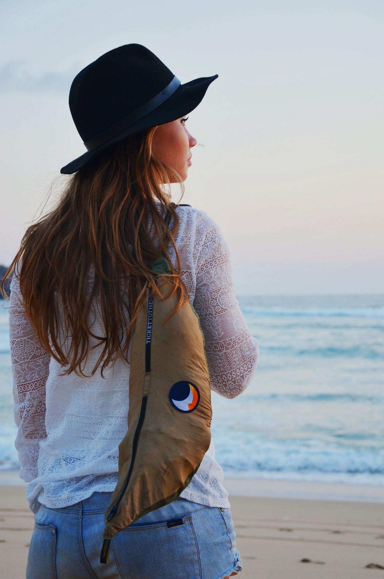 Девушка со свернутым за спиной гамаком.