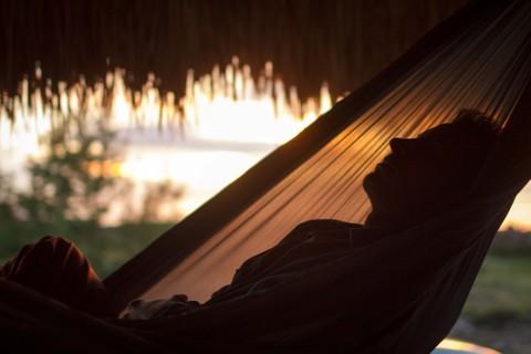 Мужчина дремлет в гамаке.
