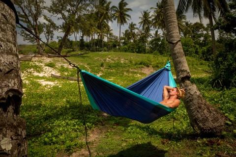 Девушка спит в гамаке.