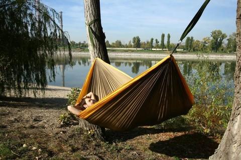 Мужчина спит в гамаке у реки.