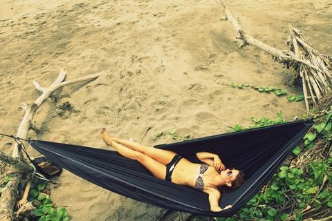Сплю в гамаке на пустынном пляже.
