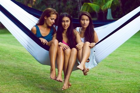Сразу три девушки сидят в одном гамаке.