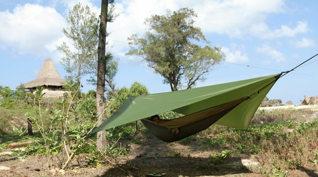 Использование тента для гамака в лесу.