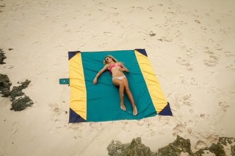 Девушка загорает на роскошном пляжном покрывале.