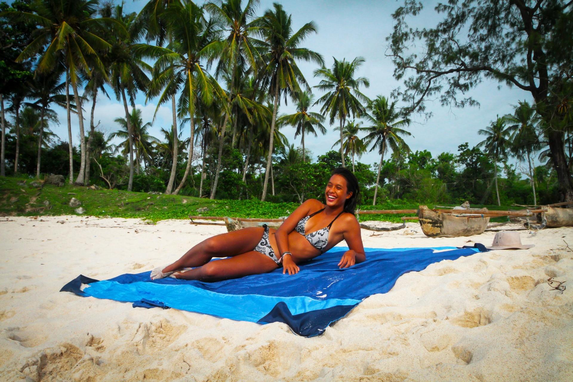 Девушка на голубом пляжном покрывале.