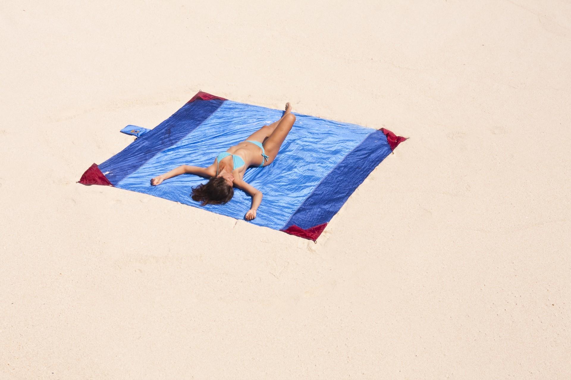 Девушка заснула на пляжном покрывале.