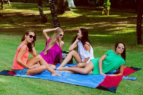Группа девушек сидит на пляжном покрывале.